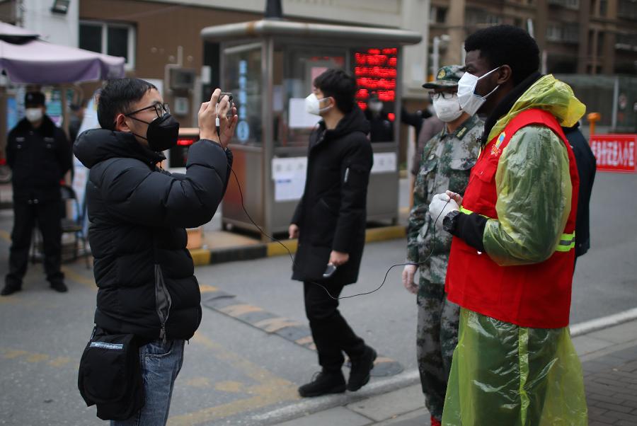 來自尼日利亞的24歲留學生歐萊德戴著口罩,為南京市民體溫測量(中新社)