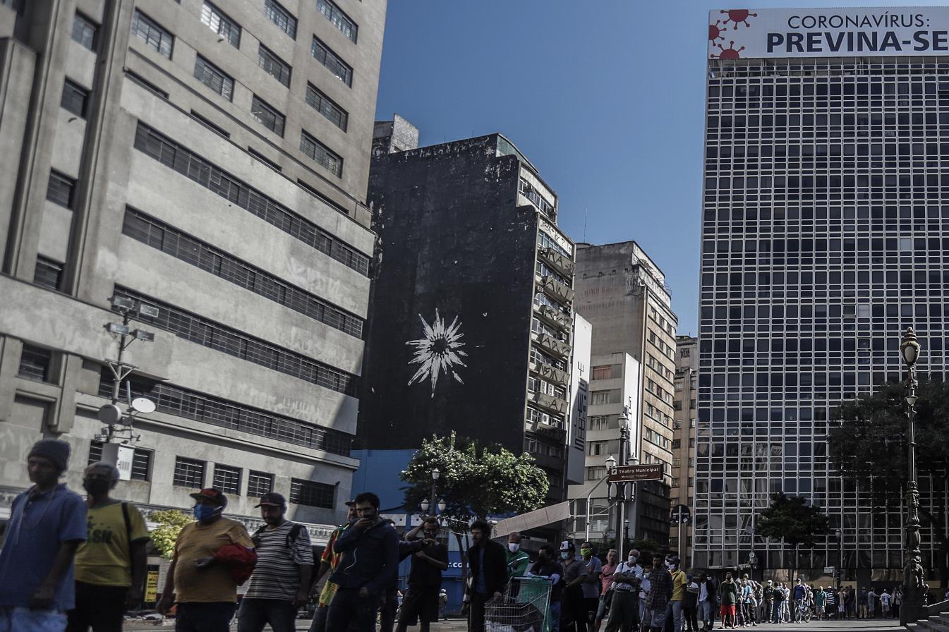 5月20日,巴西民眾在聖保羅市中心排隊領取救濟食物(新華社資料圖片)