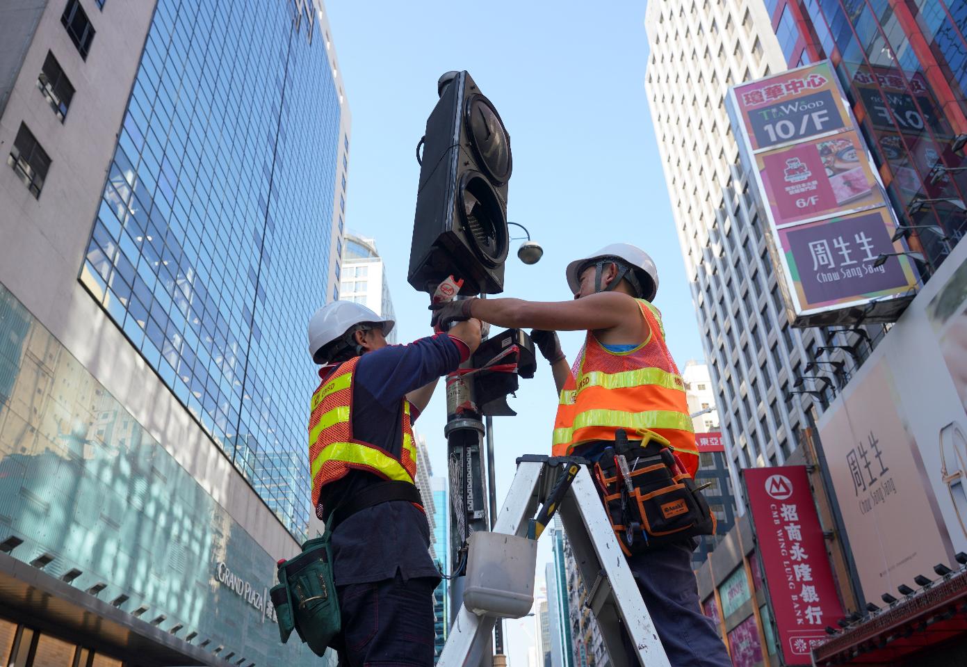 暴亂令香港傷痕累累。圖為工程人員正在維修被暴徒破壞的交通燈(中新社資料圖片)
