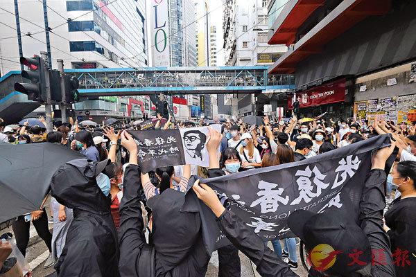 有人高舉「光復香港,時代革命」標語及梁天琦的肖像。香港文匯報記者 攝