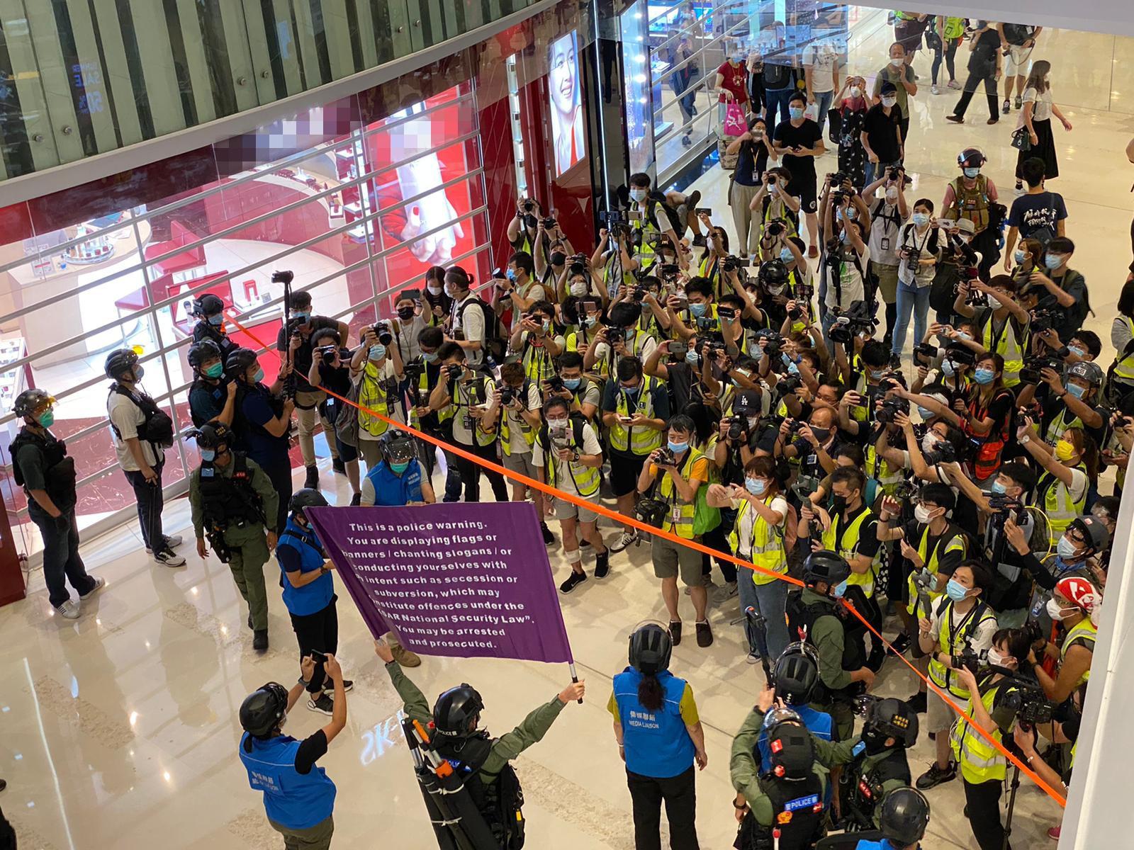 香港警方舉紫旗警告示威者,叫喊相關口號行為涉違國安法。(香港警方FB)