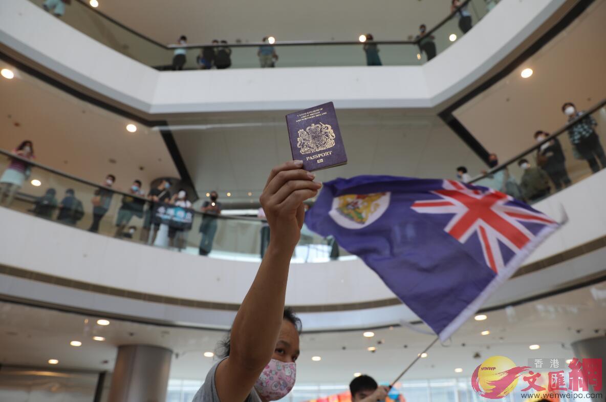 22日,示威者在IFC商場舉英國國旗和BNO護照。(文匯報)