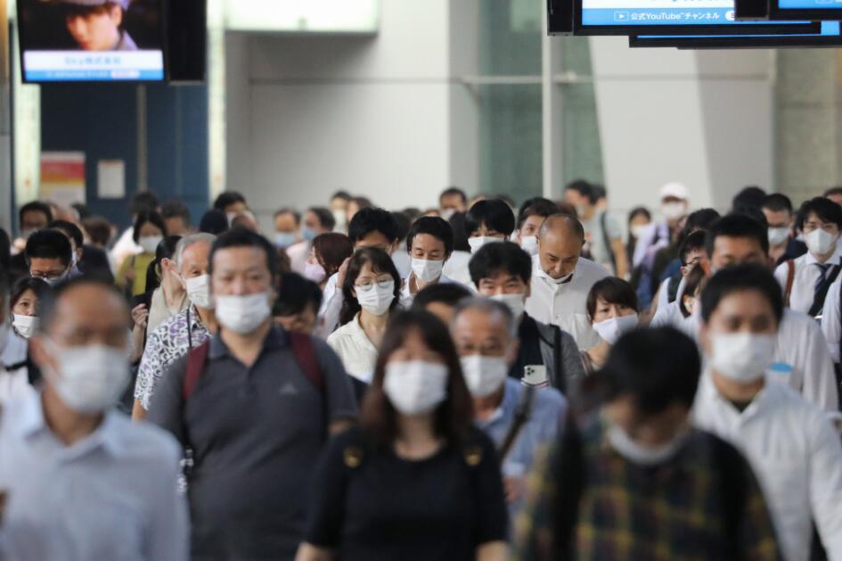 日本東京,人們戴口罩出行。日本疫情反复,近日反彈明顯。新華社