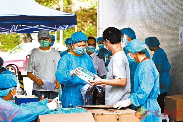 香港9月1日起啟動普及社區檢測計劃。圖為早前身穿防護衣的工作人員在黃大仙慈愛邨派發新冠病毒檢測套裝和表格。(資料圖片)