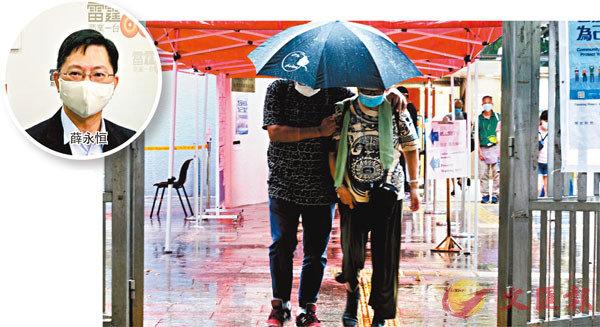 兩長者雨中相扶持,冒着紅雨接受檢測。香港文匯報記者 攝
