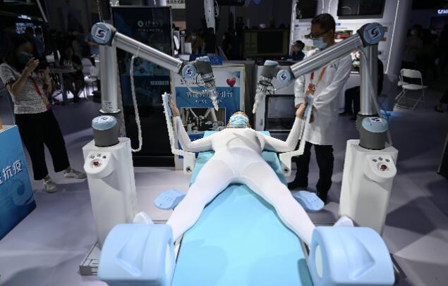 北京服貿會展區,工作人員在中醫智能經絡導引台演示機器人幫助患者按摩經絡。(中新社圖片)