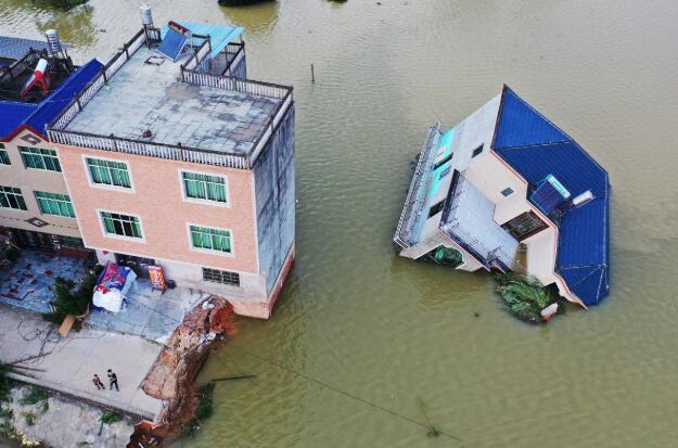 7月13日,江西鄱陽縣荻溪村樓房被洪水侵襲,整體傾斜倒下。(中新社資料圖片)